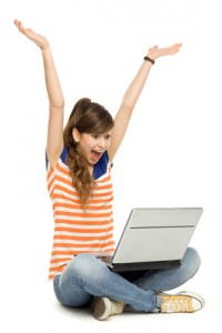 Woman with arms raised using laptop